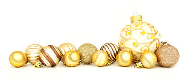 Golden Christmas baubles. Group of gold Christmas baubles arranged as a border over white Stock Images