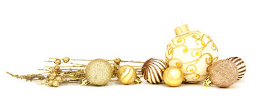 Golden Christmas baubles. Group of gold Christmas baubles and branches arranged as a border over white Royalty Free Stock Image