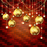 Golden Christmas baubles on a brick wall Stock Photos