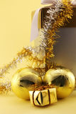 Golden Christmas baubles and a gift Stock Photography
