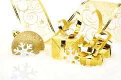 Golden christmas baubles, gifts,snowflakes with golden ribbon on snow Stock Photos