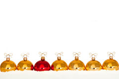 Golden christmas baubles in the snow Stock Image