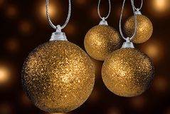 Golden christmas baubles on strings Royalty Free Stock Photography