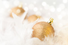 Golden Christmas Baubles. In white feather Stock Image