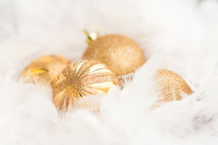 Golden Christmas Baubles. In white feather Stock Photos