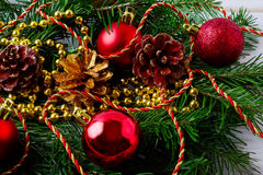 Golden Christmas beads, fir branches and red ornaments Royalty Free Stock Photos