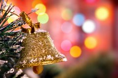 Golden Christmas bell hanging on the snow-covered pine branch of Bokeh Stock Images