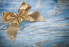 Golden Christmas bow with bell on wooden board celebrations conc Royalty Free Stock Photos