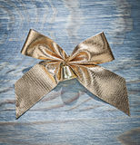 Golden Christmas bow on wooden board celebrations concept Stock Photos