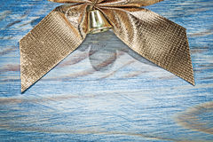 Golden Christmas bow on wooden board holidays concept Stock Image