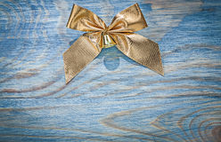 Golden Christmas bow on wooden board top view celebrations conce Royalty Free Stock Image