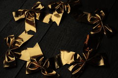 Golden Christmas bows on wooden background. holiday miracle  soon begin. Royalty Free Stock Images