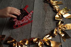 Golden Christmas bows on wooden background.  miracle will soon begin. Golden Christmas bows on wooden background. holiday miracle will soon begin Stock Photo