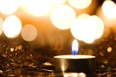 Golden Christmas candlelight. Christmas candlelight decoration against blurred background of bright lights Stock Image