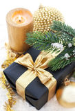 Golden Christmas composition with gift box, candle and branch of Royalty Free Stock Photos