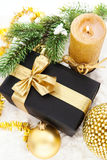 Golden Christmas composition with gift box, candle and branch of Royalty Free Stock Photography