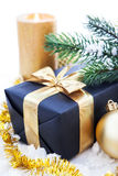 Golden Christmas composition with gift box, candle and branch of Royalty Free Stock Photo