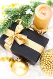 Golden Christmas composition with gift box, candle and branch of Royalty Free Stock Image