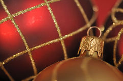 Golden christmas decoration on festivered backgrou. Red and gold frosted christmas baubles stock photos