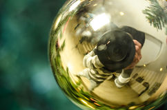 Golden Christmas decoration with reflection of photographer - Soft focus Stock Photography