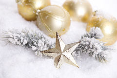 Golden Christmas decoration with snow. Golden Christmas decoration and pine with a star covered with snow royalty free stock image