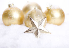 Golden Christmas decoration with snow. Golden Christmas decoration and pine with a star covered with snow stock photography