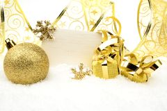 Golden christmas decoration on snow with wishes card Royalty Free Stock Image