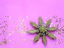 Golden Christmas decoration snowflake on a pink background top view. Christmas holiday mood. Magic and fairy tale stock photography