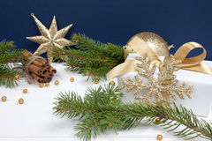 Golden Christmas decoration on white wood. Golden Christmas decoration with golden ball, golden star, pine branches and cinnamon on white wood stock photo