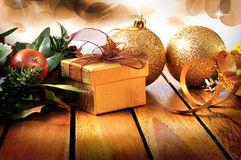 Golden Christmas decoration on wooden table with balls and gift Stock Photography