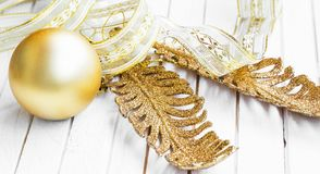 Golden Christmas decorations with balls and ribbon on wooden bac Stock Photos