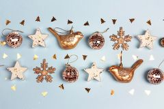 Golden Christmas decorations on blue background. Composition of royalty free stock image