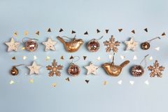 Golden Christmas decorations on blue background. Top view, flat stock photos