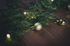 Golden Christmas decorations and pine branches on a wooden vintage background Royalty Free Stock Photography