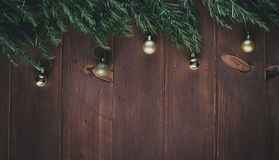 Golden Christmas decorations and pine branches on a wooden vintage background Royalty Free Stock Images