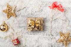 Golden Christmas decorations on snowy background Royalty Free Stock Photo