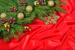 Golden Christmas decorations and spruce branch and cones on a re. D background Stock Photo