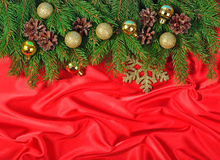 Golden Christmas decorations and spruce branch and cones on a re. D background Royalty Free Stock Photo