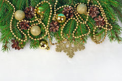 Golden Christmas decorations and spruce branch and cones on a wh. Ite background Royalty Free Stock Photo
