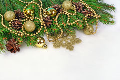 Golden Christmas decorations and spruce branch and cones on a wh. Ite background Royalty Free Stock Photography