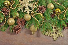 Golden Christmas decorations and spruce branch and cones. On a wooden background Royalty Free Stock Photography