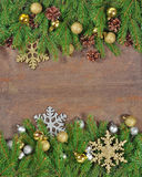 Golden Christmas decorations and spruce branch and cones. On a wooden background Stock Photos