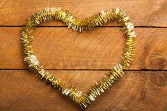 Golden Christmas garland in heart shape on wood Stock Images