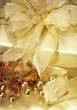 Golden Christmas Gift. Beautifully Wrapped Christmas Gift with a Golden Ribbon. Shallow DoF royalty free stock photos