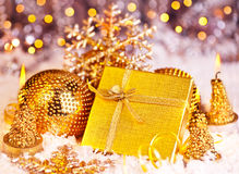 Golden Christmas gift with baubles and candles Royalty Free Stock Photos