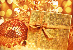 Golden Christmas gift with baubles decorations Stock Photography