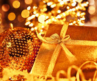 Golden Christmas gift with baubles decorations Royalty Free Stock Image