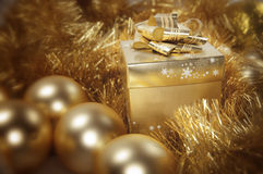 Golden christmas gift and baubles Royalty Free Stock Photo