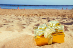 Golden christmas gift on beach Stock Image