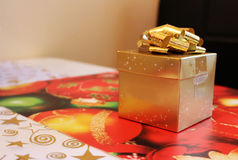 Golden christmas gift box with wrapped surprise. Photo of golden christmas gift box with wrapped surprise stock images